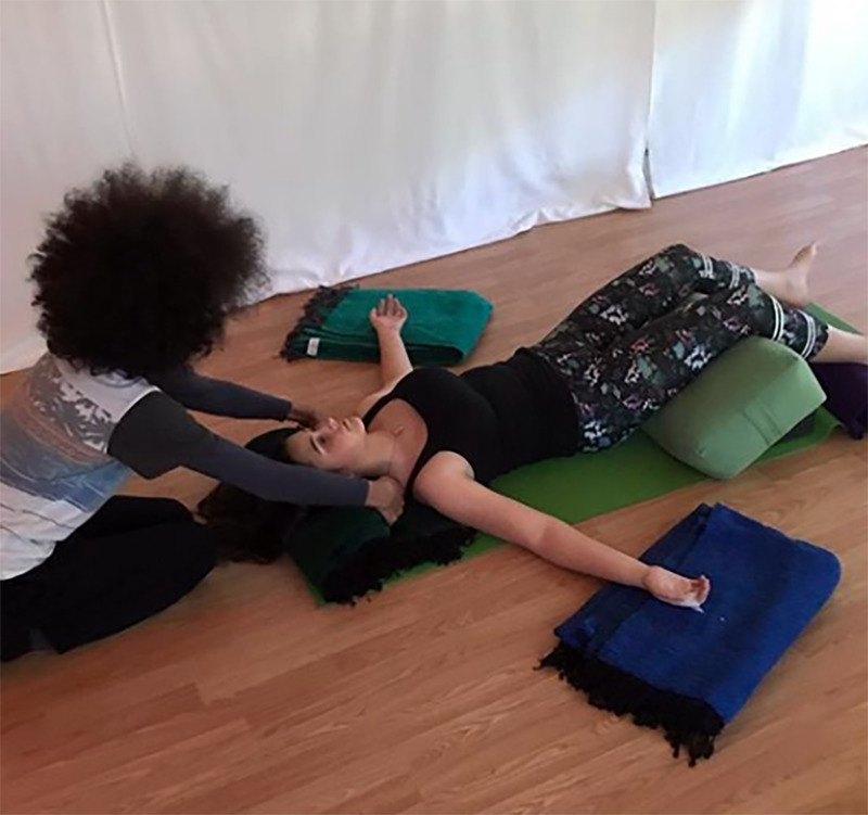 Tabay instructs a woman in restoration yoga.