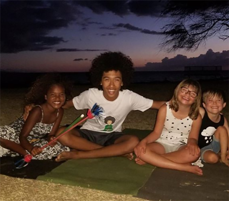 Tabay poses with younger children on yoga mats.