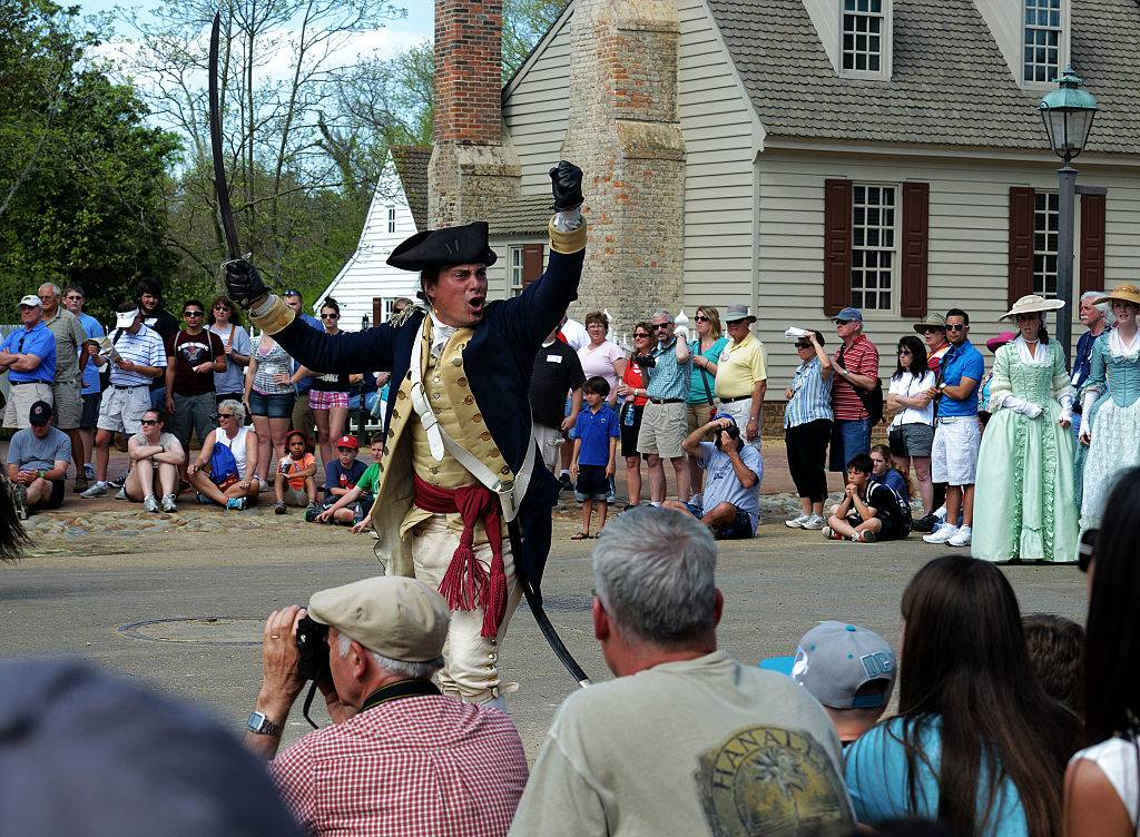 a costumed man shouting at tourists in colonial williamsburg