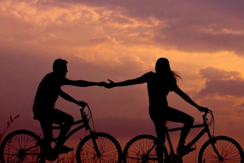A silhouette shows a couple reaching a hand to one another while riding a bike.