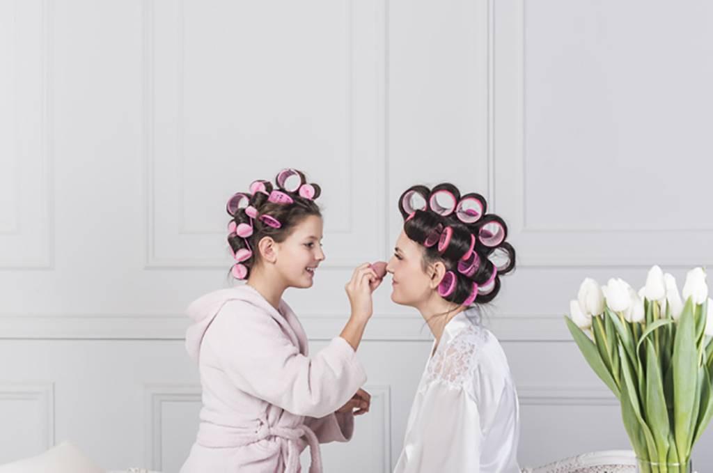 Daughter putting makeup on woman