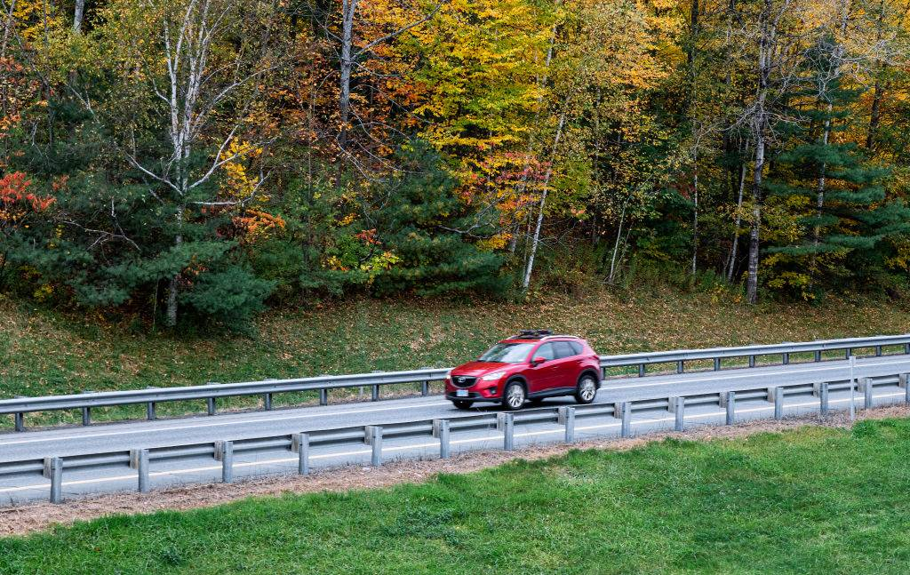 a red car driving near autumn leaves