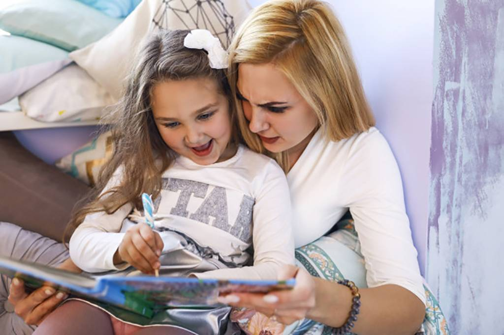 Woman and daughter writing together