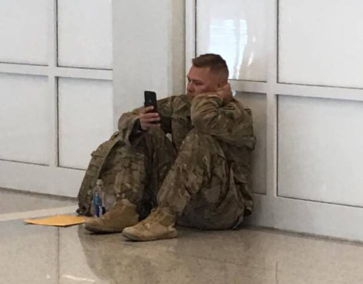 Brooks sits on the ground in the airport and watches his phone.