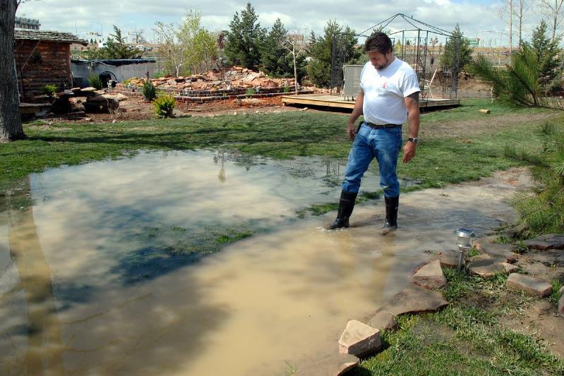 A man wades through his flooded lawn.