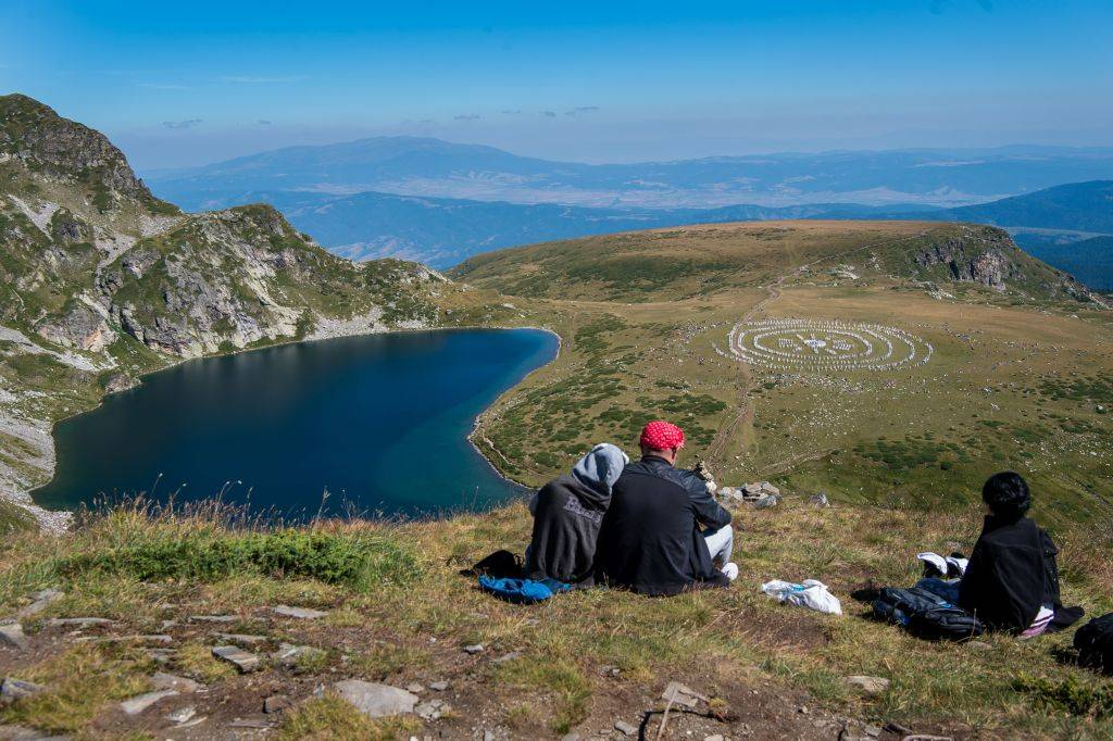 People watch members of an international religious movement called the White Brotherhood performing ritual dance on the top of the Rila Mountain, near Babreka lake
