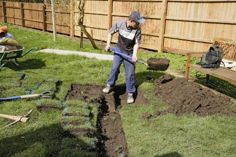 A gardener digs a trench to drain his garden.