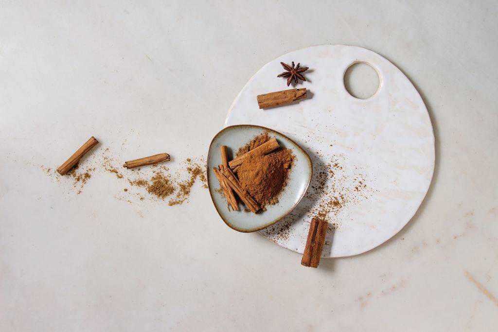 a plate with cinnamon sticks and powder