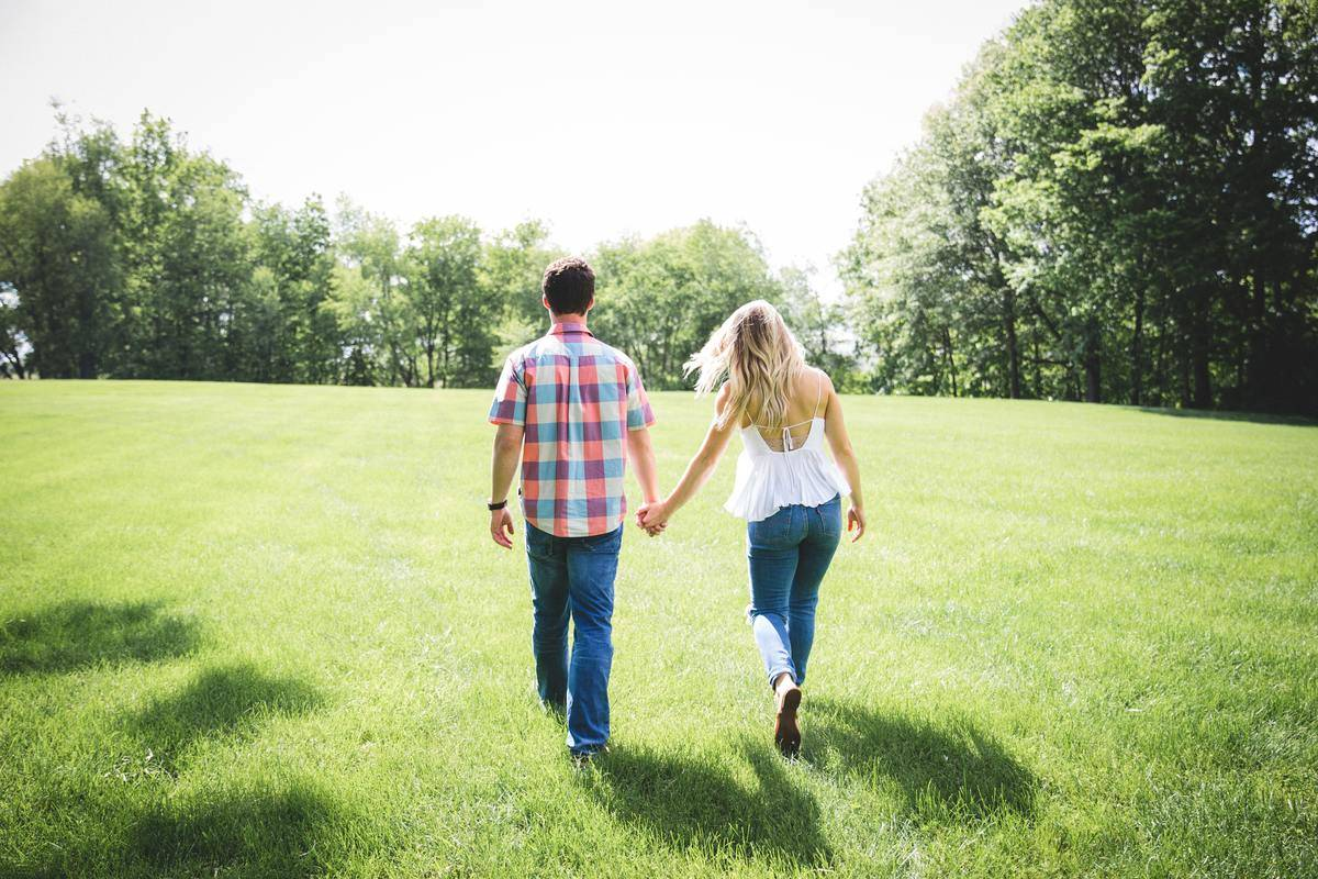 couple walking through grass holding ahdns
