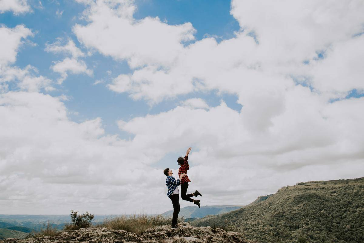 man and woman on mountain woman jumping