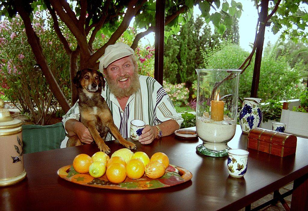 a man and his dog at a table full of lemons