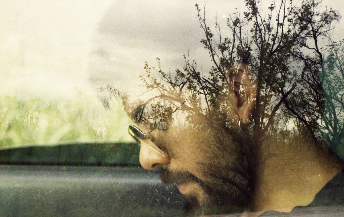 man in car with plants reflecting against glass over his head