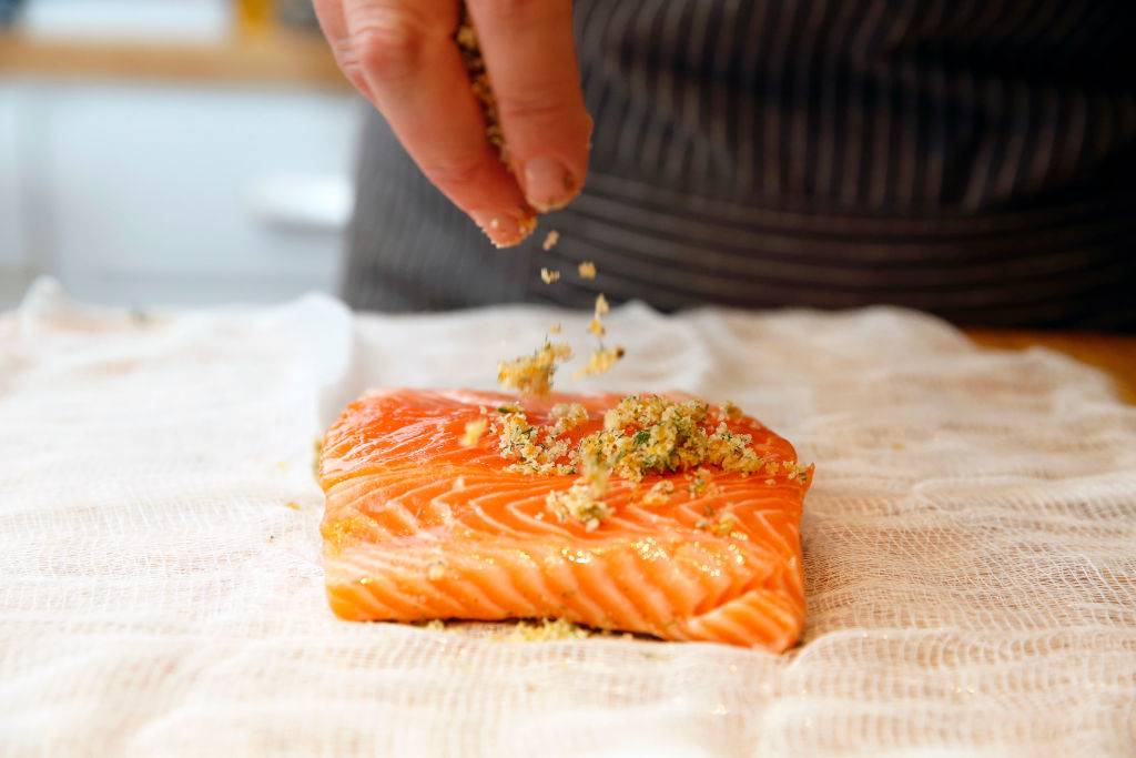 someone sprinkling bread crumbs on a piece of raw salmon