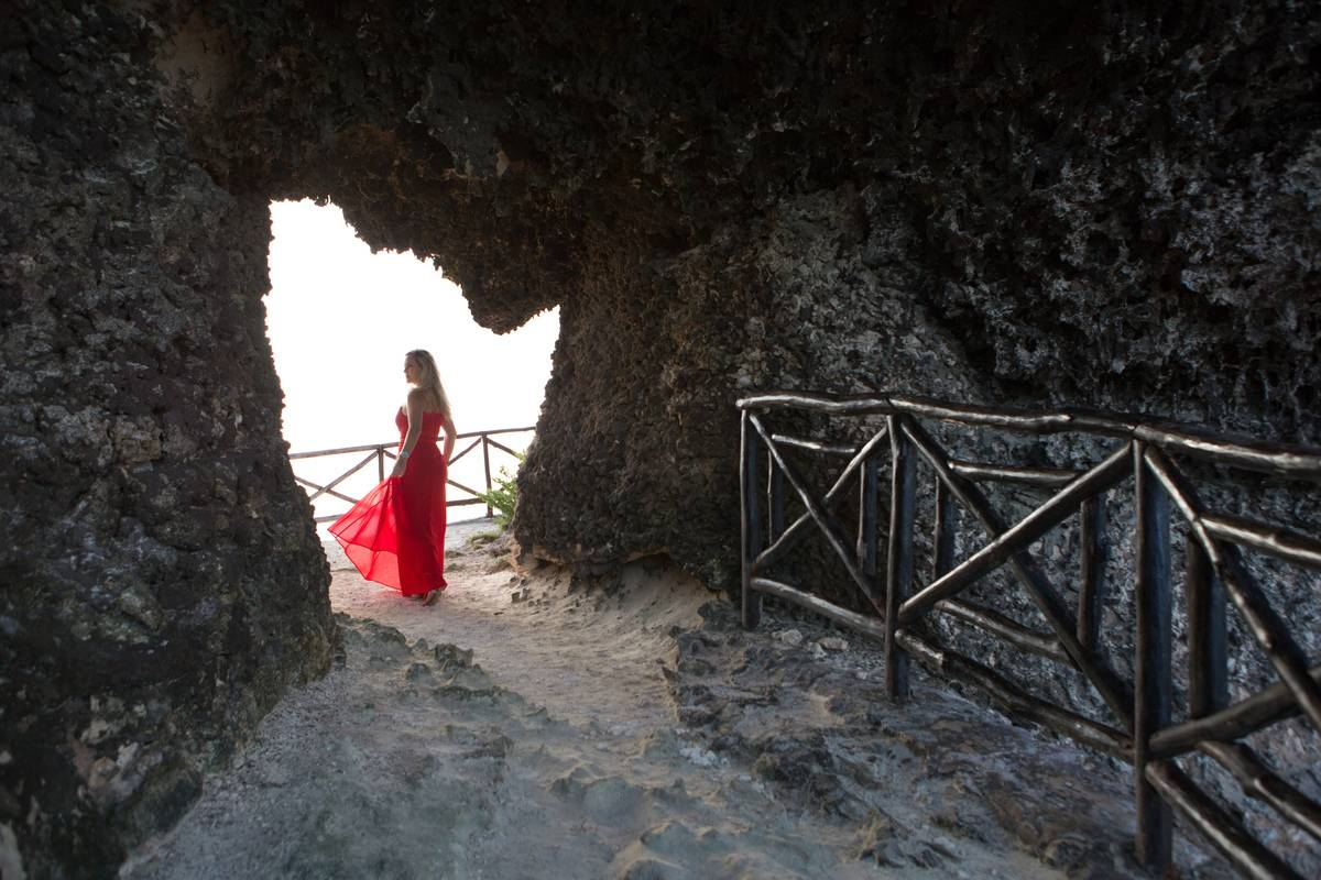 woman in red dress standing in hole in rock wall