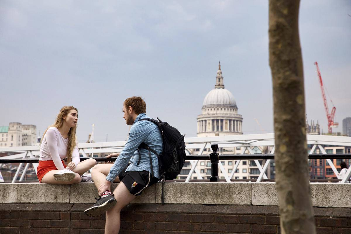 man and woman sitting on wall talking