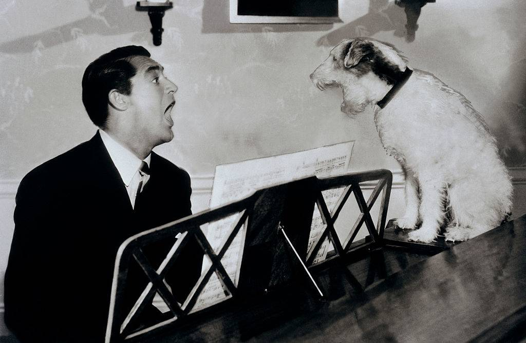 Cary Grant singing with Skippy the famous movie dog at a piano