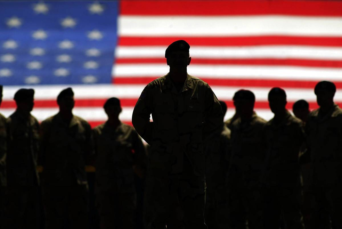 Members of the United States Army Fourth Infantry Division stand in front of the American flag.