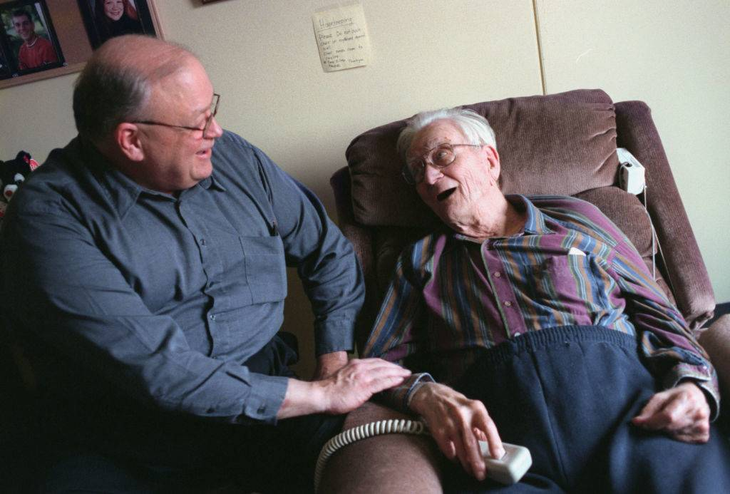 A man visits his father at a nursing home.