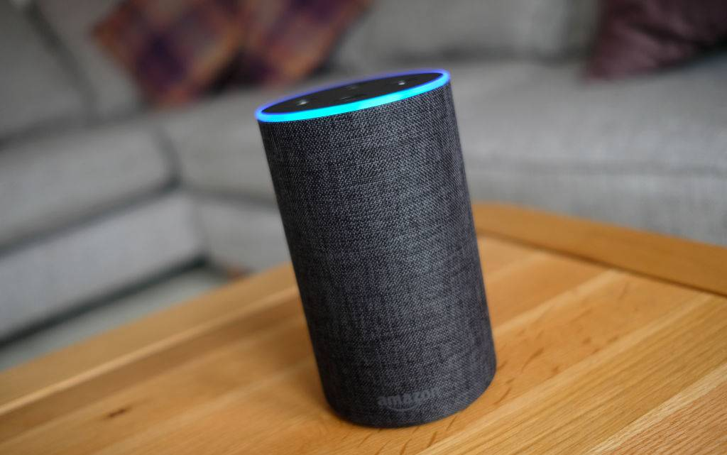 An amazon echo sits on a coffee table.