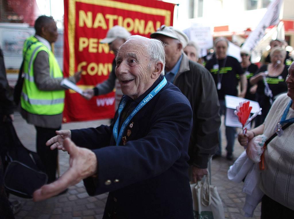 An elderly man smiles at someone.