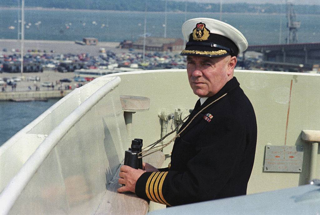 A captain looks to sea from a ship.