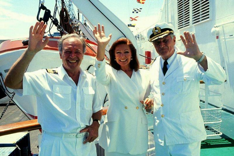 Cruise crew members smile and wave to the camera.
