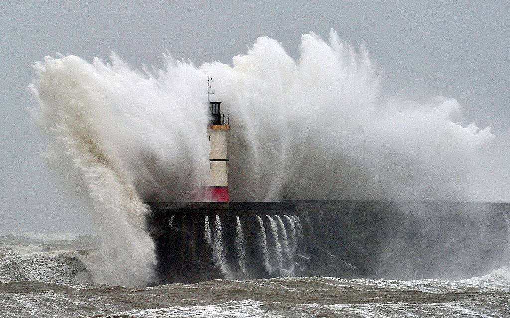 Waves crash against a lighthouse.