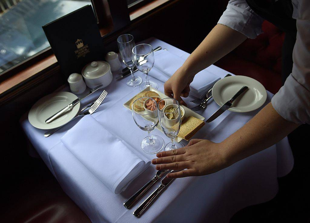 A waitress sets a dining table.