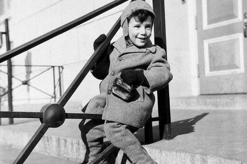 A boy sits on a building stoop in Brooklyn.