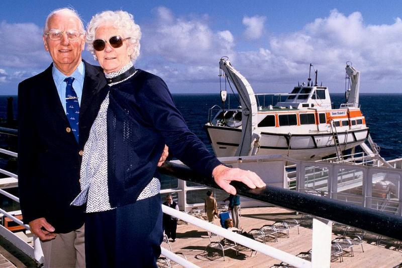 An elderly couple stands aboard a ship.
