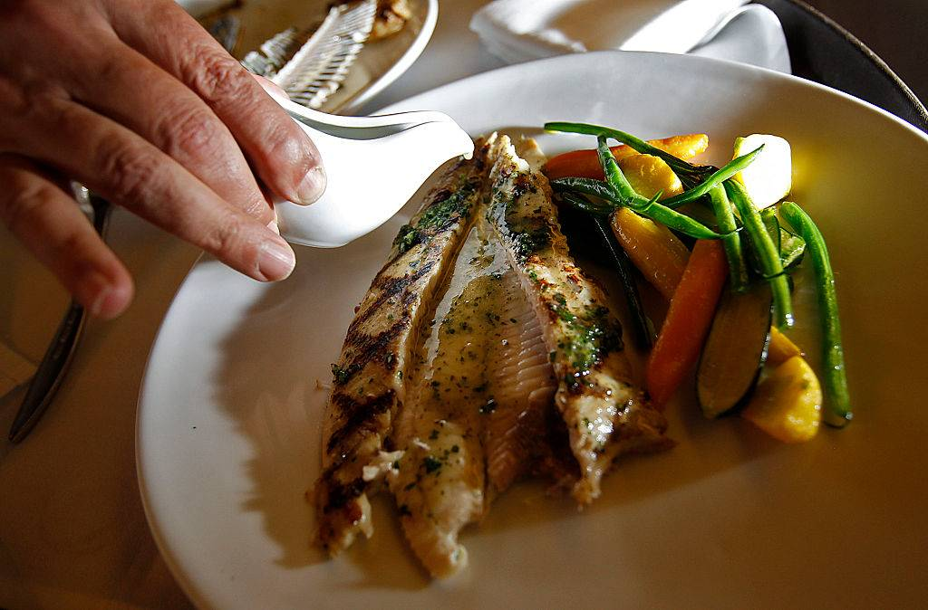 Sauce is poured over a grilled dover sole.