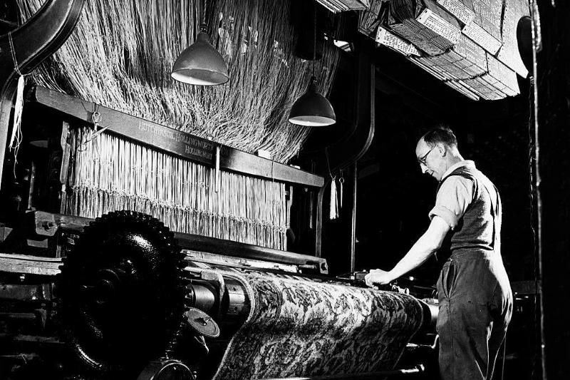 A textile worker operates a machine.