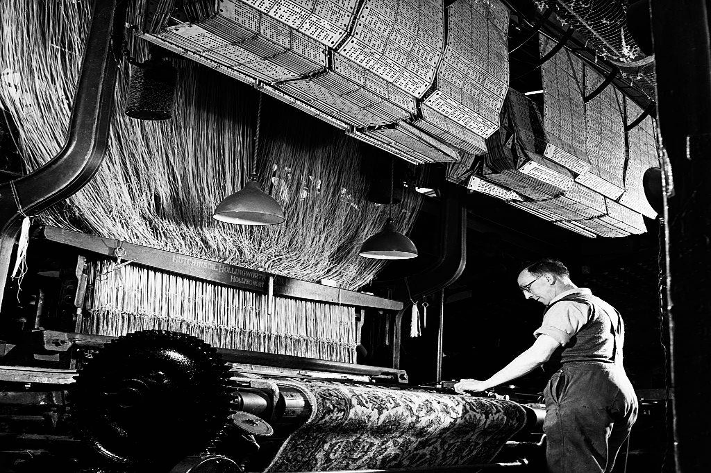 A textile worker operates a machine.