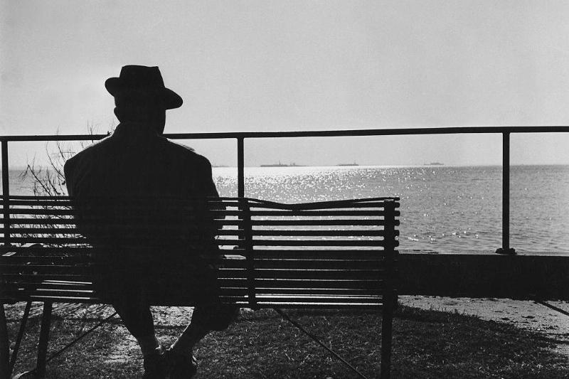 An old man sits on a bench by himself.