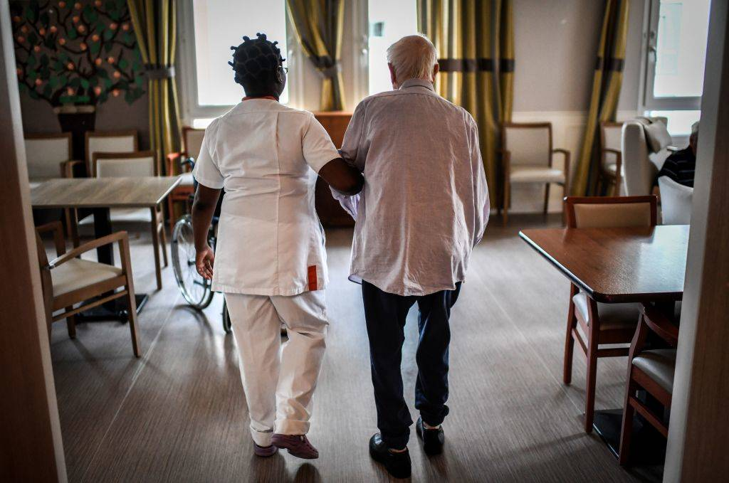 An elderly man walks with the assistance of a nurse.