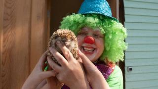 a woman dressed as a clown holding a hedgehog