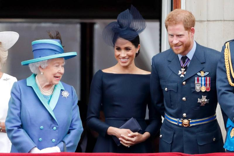 Queen Elizabeth II, Meghan, Duchess of Sussex and Prince Harry, Duke of Sussex watch a flypast to mark the centenary of the Royal Air Force from the balcony of Buckingham Palace