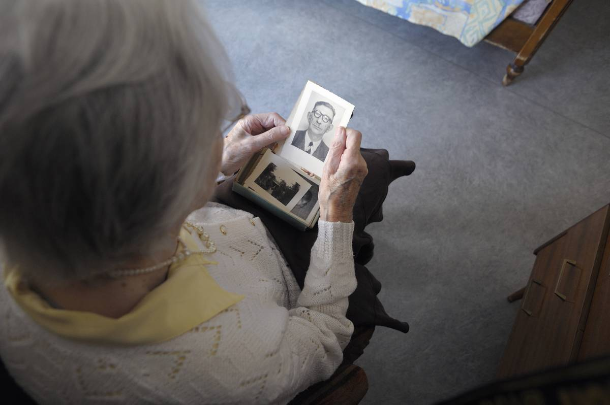 A woman with Alzheimer's looks through old photos.