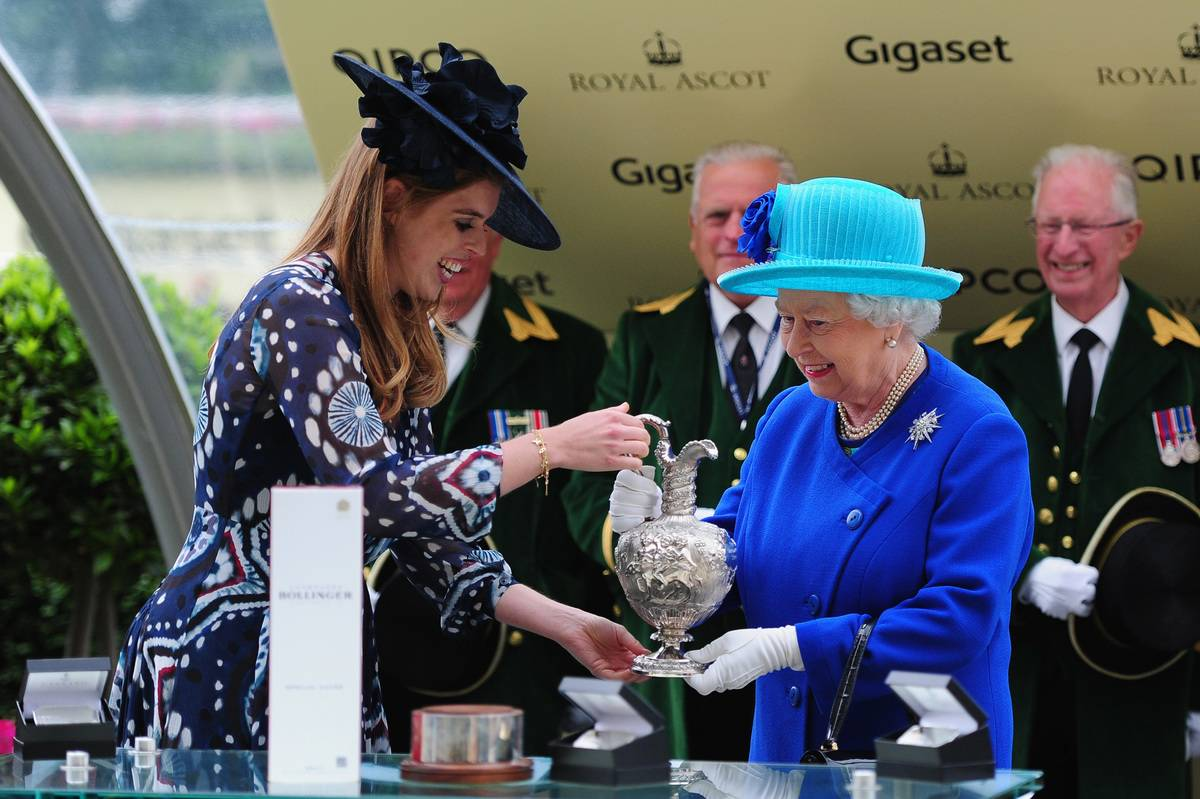 Queen Elizabeth II smiles as she is presented the Hardwicke Stakes trophy by Princess Beatrice
