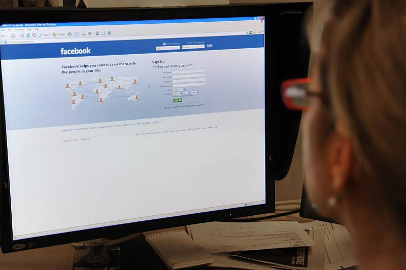 A woman prepares to log on to the Facebook