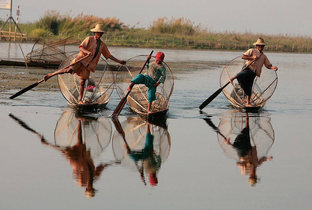fishermen in myanmar paddling in the water