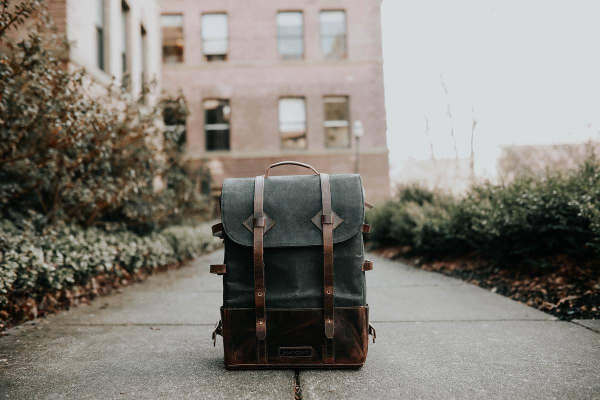 A backpack sits on a sidewalk.