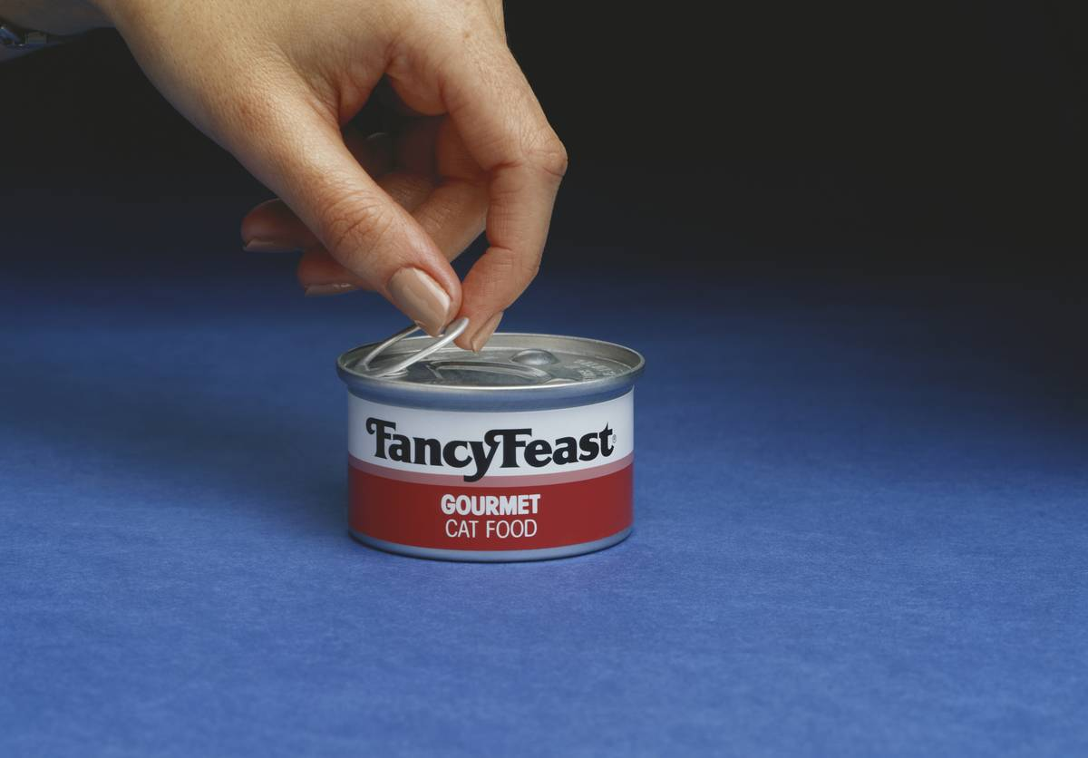 A person opens a can of Fancy Feast cat food.