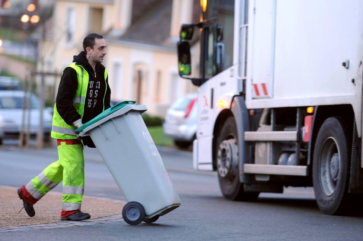 A garbage man pushes a bin.