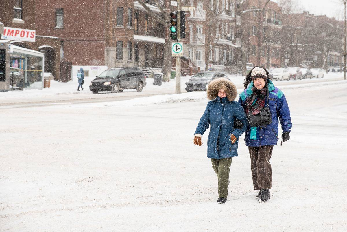 A man and woman walk in the snow in Quebec, Canada.
