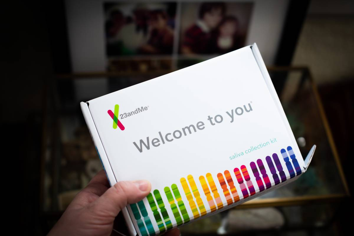 A person holds a 23andMe DNA testing kit.