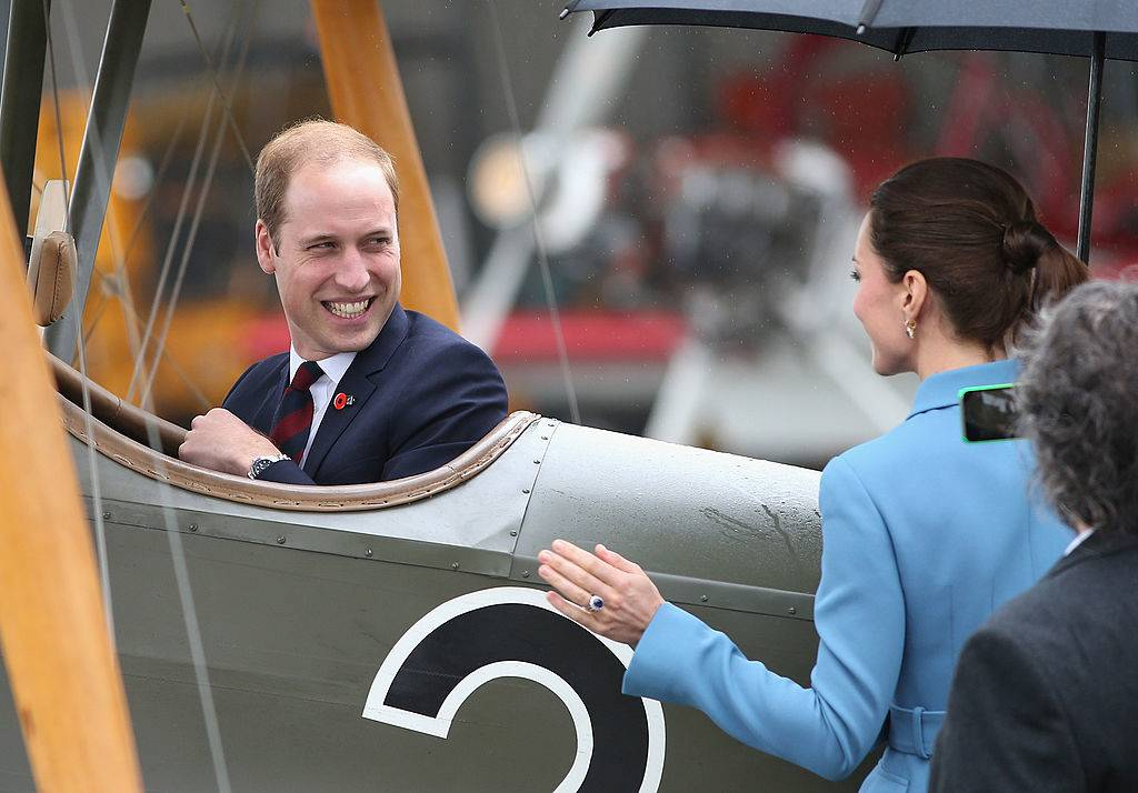 Prince William, Duke of Cambridge turns round and laughs to Catherine, Duchess of Cambridge and Sir Peter Jackson as he sits in a World War I Bi-plane