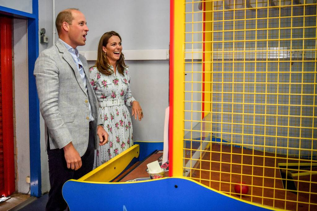 Prince William, Duke of Cambridge and Catherine, Duchess of Cambridge laugh after throwing balls to knock down figures on an arcade game