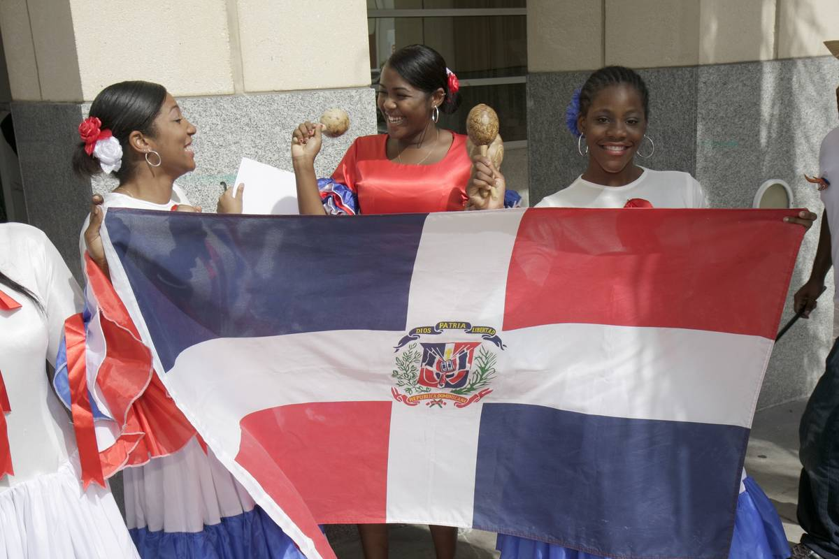 Women hold a Dominican Republic flag at the Miami Book Fair International parade.