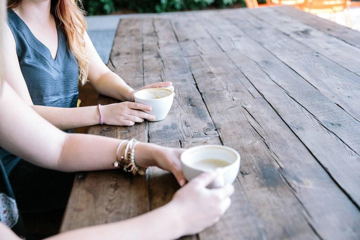 Two friends drink coffee.
